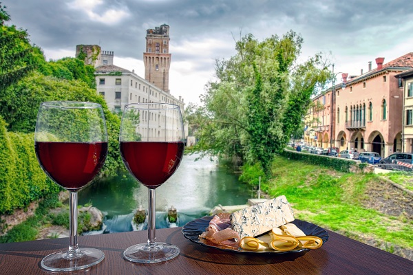 Two glasses of red wine with cheese and meat snacks with view of canal in Italy.
